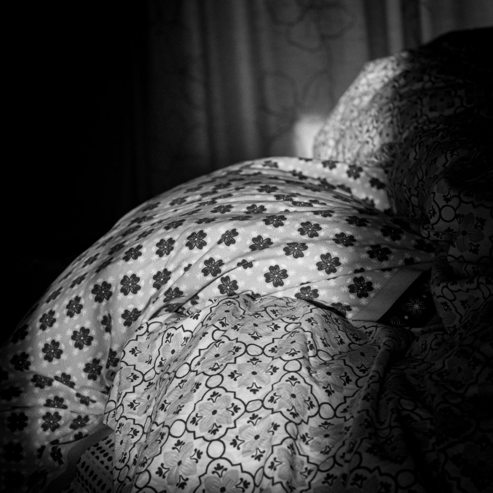 Photo of Slant of Light #4, a study of light and shadows across an unmade bed